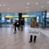 pic-of-a-guy-waiting-for-someone-at-an-airport-with-a-sign-that-says-godot